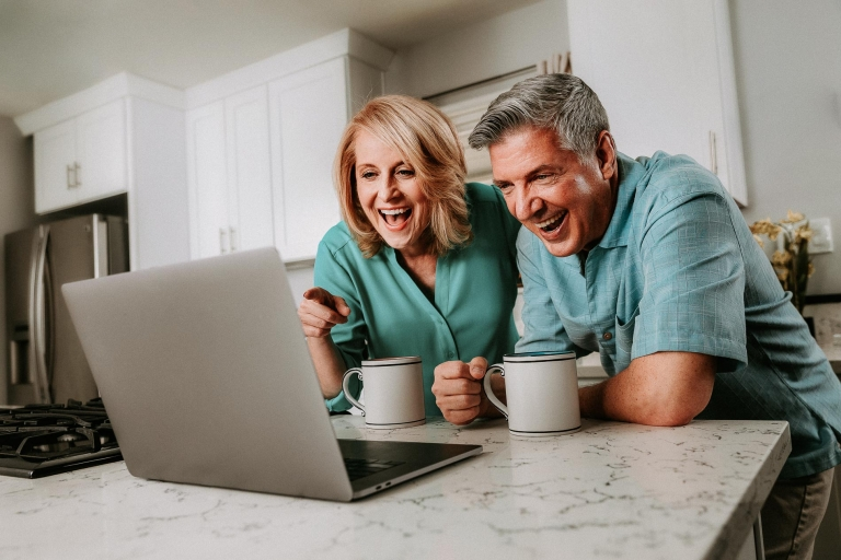 Smiling and laughing retired seniors video chatting with family